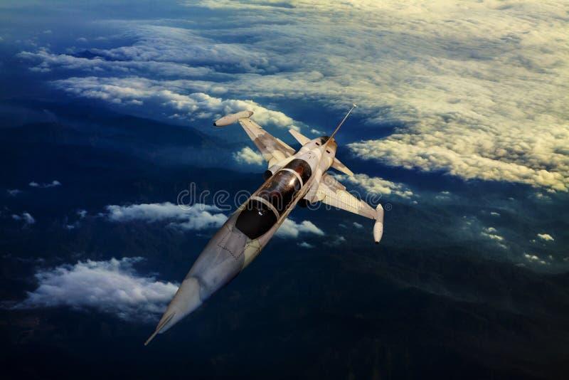 Militärdüsenflugzeug, das über Gebirgslandansicht unten fliegt lizenzfreie stockfotos