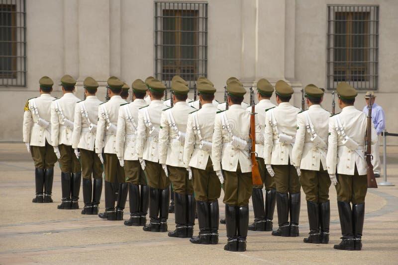 Militären av Carabinerosen sätter band deltar i ändrande vaktceremoni framme av den LaMoneda presidentpalatset, Santiago, Chile arkivfoton