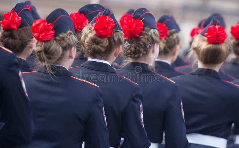 Militären ståtar och flickor som medlemmar av krigsmakt och polisen royaltyfria foton