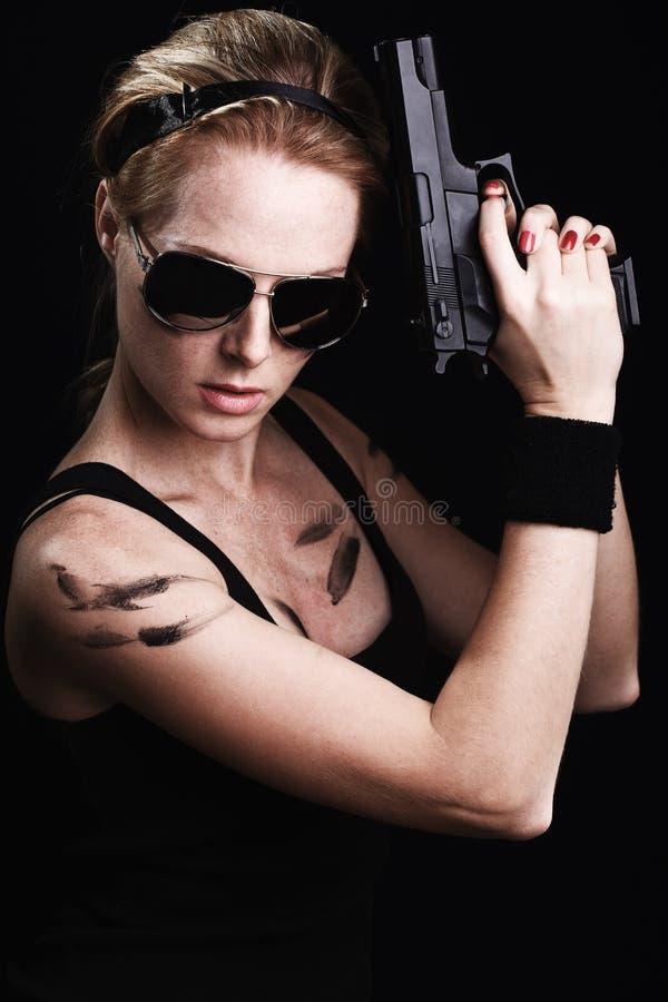 Militärfrau, die mit Gewehr aufwirft lizenzfreie stockfotografie