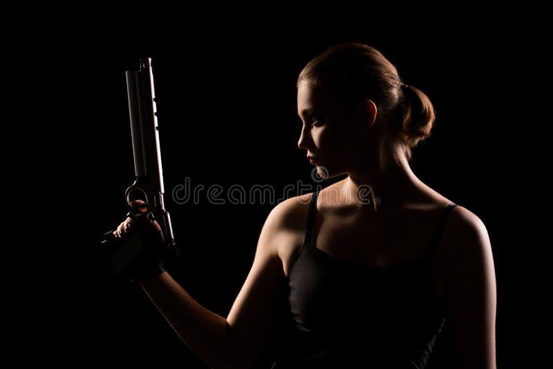 Militärfrau mit einem Gewehr über schwarzem Hintergrund stockfotografie
