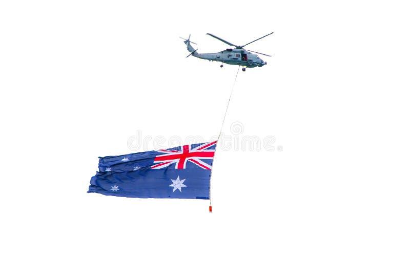 Militärhubschrauberfliegen mit dem australischen Flaggenhängen lokalisiert auf weißem Hintergrund stockbild