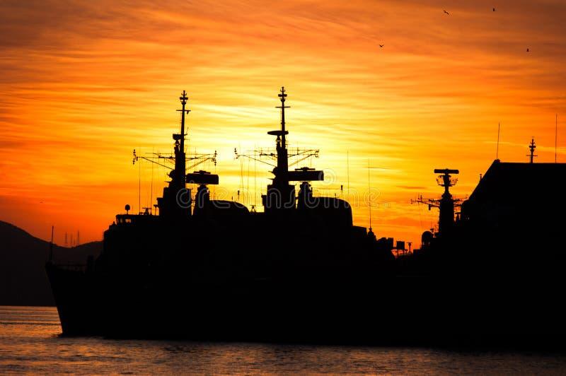 Militärmarine-Schiffs-Schattenbilder durch Sonnenuntergang stockbild