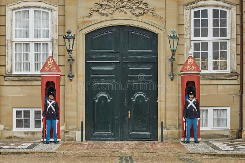 Militärofficerare som står vakt utanför Amalienborgpalatset i Köpenhamn, Danmark royaltyfri bild