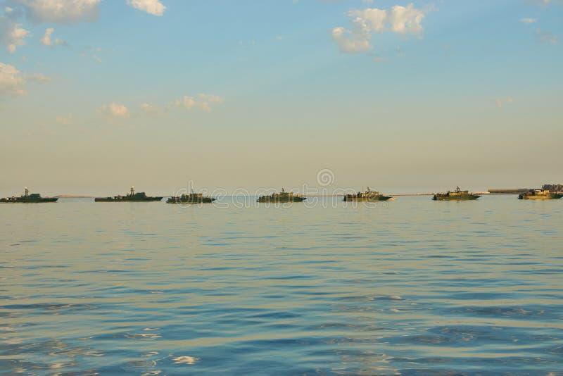 Militärschlachtschiffe in einem Meer bellen zur Sonnenuntergangzeit stockbild