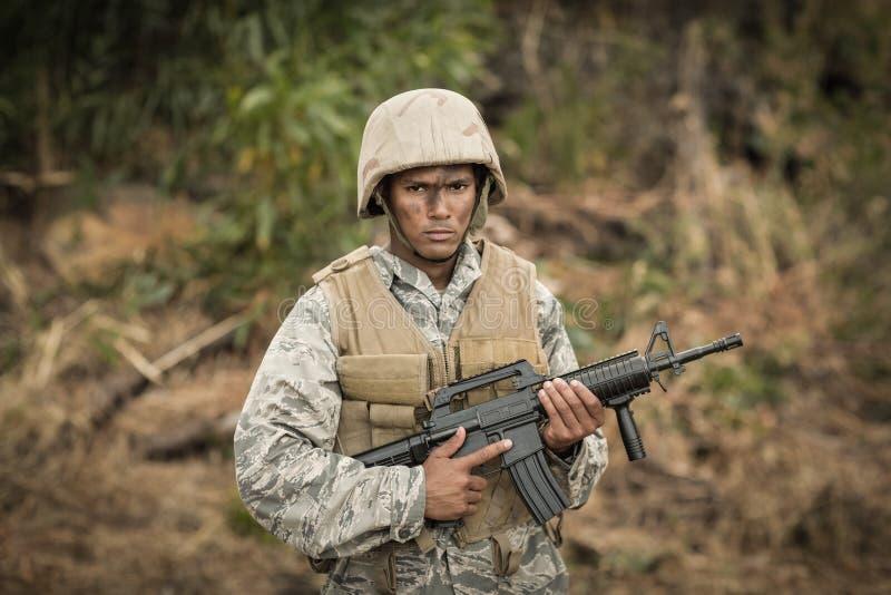 Militärsoldat, der mit einem Gewehr in einem Ausbildungslager schützt stockfotos