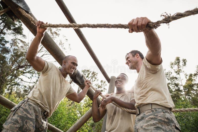 Militärsoldaten, die während des Hindernistrainings aufeinander einwirken stockfotografie