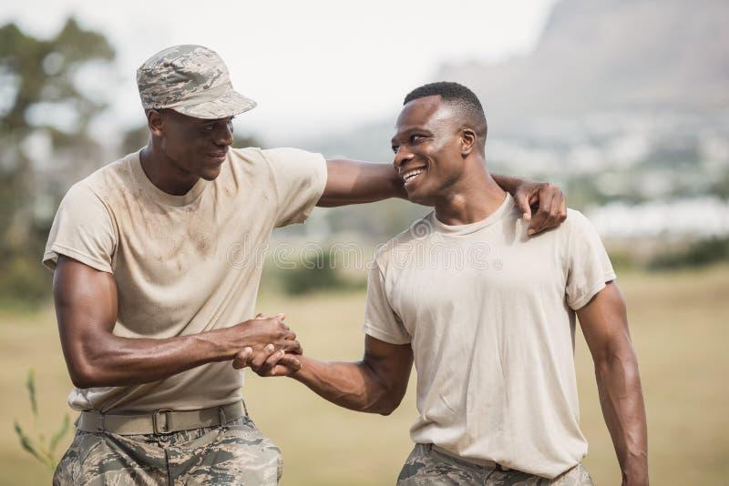 Militärsoldater som skakar händer under hinderkurs royaltyfri foto