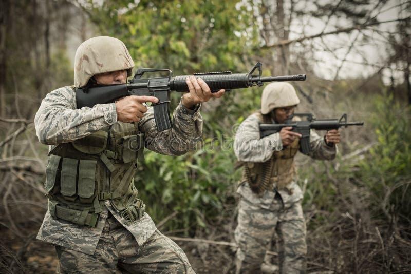 Militärsoldater under utbildningsövning med vapnet royaltyfri foto