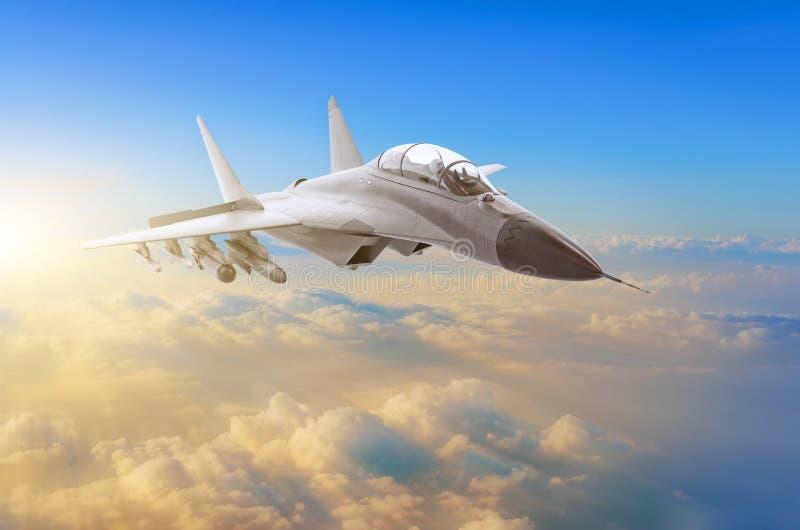 Militärt kämpeflygplan på den hög hastigheten som högt flyger i himmelsolnedgången royaltyfri foto