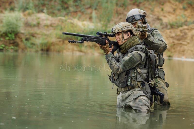 Militärt lag som korsar floden under brand arkivfoto
