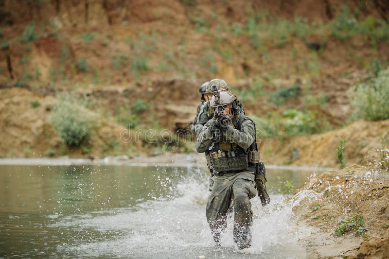 Militärt lag som korsar floden under brand royaltyfri fotografi