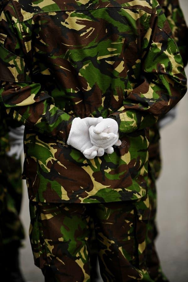 Militair in camouflage eenvormig met handen achter zijn rug stock foto