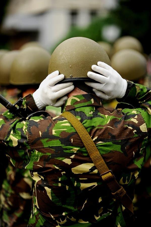 Militair in camouflage eenvormige schikkende hallo helm stock foto's