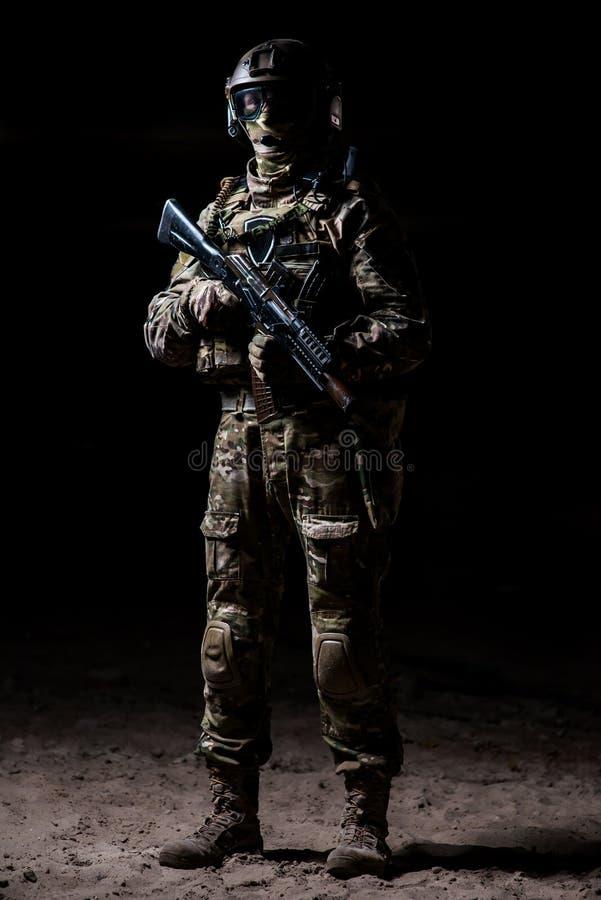 Militair in camouflage met een geweer die zich op een peloton en horloges bevinden stock foto's