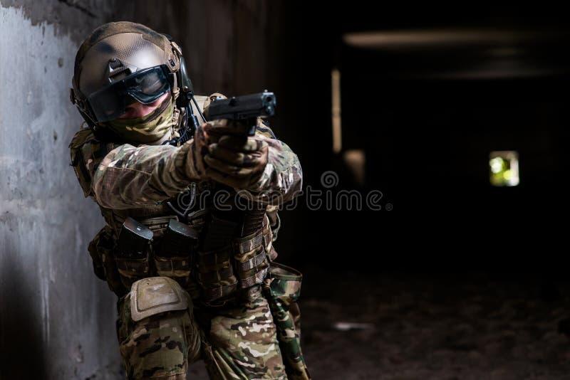 Militair die een kanon in zijn hand en het streven houden stock foto