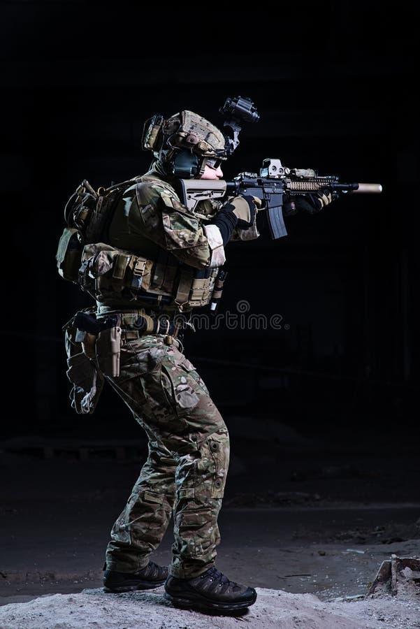 Militair die van geweer op donkere achtergrond streven royalty-vrije stock fotografie