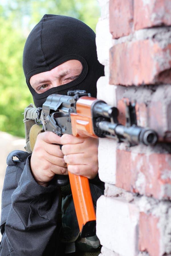 Militair die in zwart masker met een kanon richt stock foto's