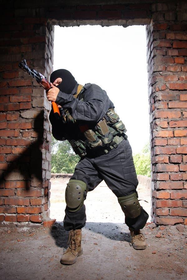 Militair die in zwart masker met een kanon richt royalty-vrije stock foto