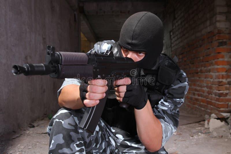 Militair die in zwart masker met een kanon richt stock foto