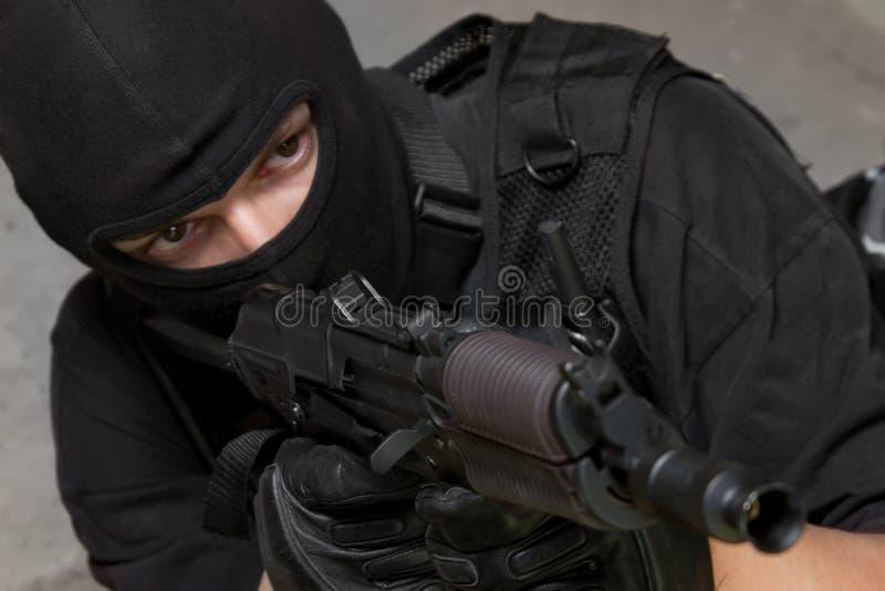 Militair die in zwart masker met geweer ak-47 richt stock foto's
