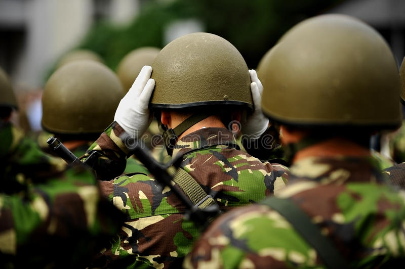 Militair in eenvormige camouflage schikkend zijn helm royalty-vrije stock foto