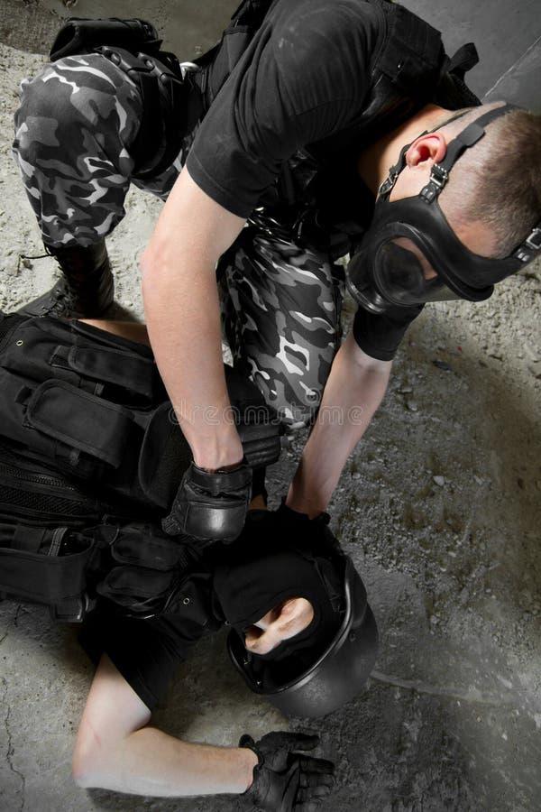 Militair in gasmasker dat zijn gewonde partner redt stock foto