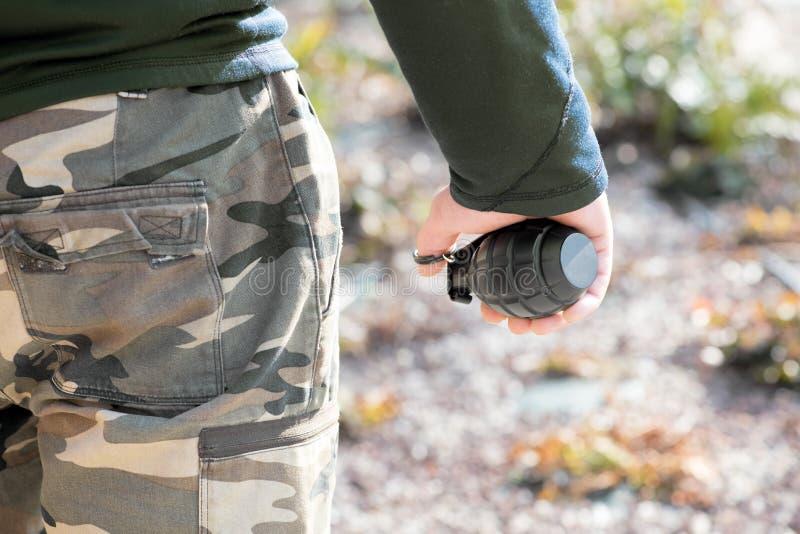 Militair of mens die in camouflage een granaat houden royalty-vrije stock fotografie