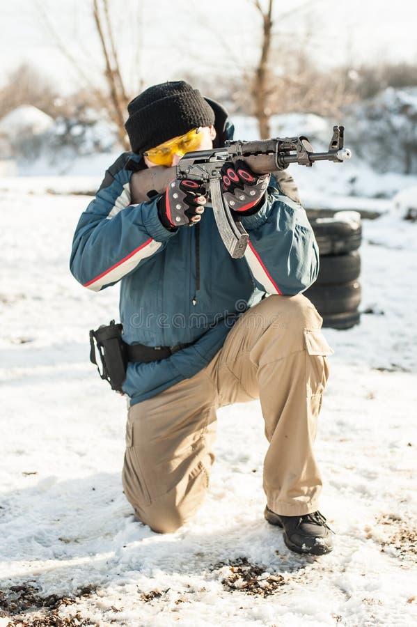 Militair met kalashnikovriffle machinegeweer op openlucht het schieten waaier stock fotografie