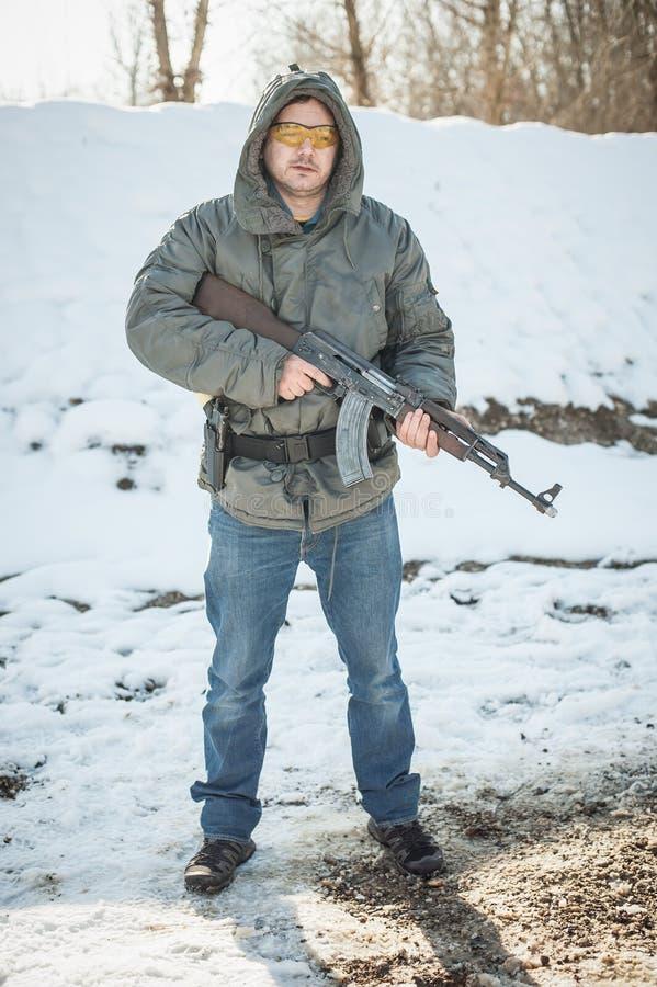Militair met kalashnikovriffle machinegeweer op openlucht het schieten waaier royalty-vrije stock foto's
