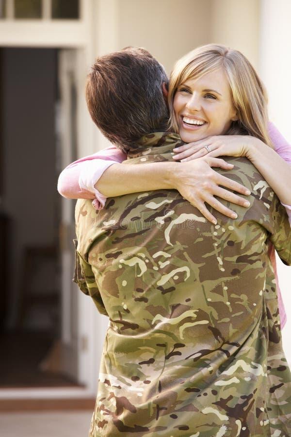 Militair Returning Home And door Vrouw wordt begroet die royalty-vrije stock afbeelding