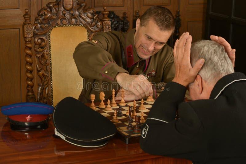 Militair rijp algemeen het spelen schaak met militair royalty-vrije stock afbeeldingen