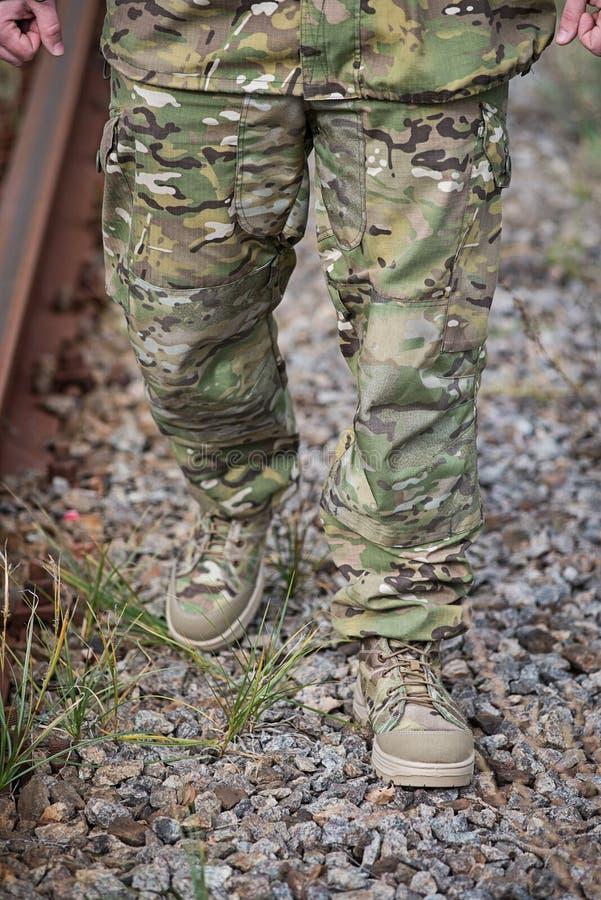 Militair` s benen tegen de achtergrond van de weg stock foto's