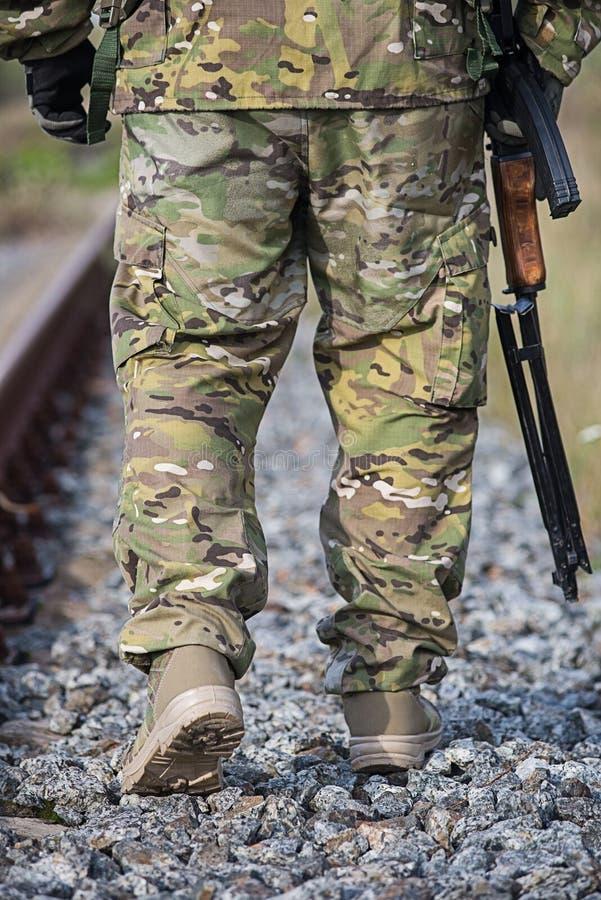 Militair` s voeten met wapens op de weg stock foto's