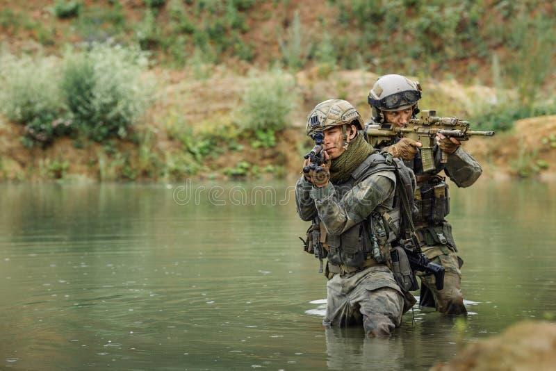 Militair team die de rivier kruisen onder brand stock foto's