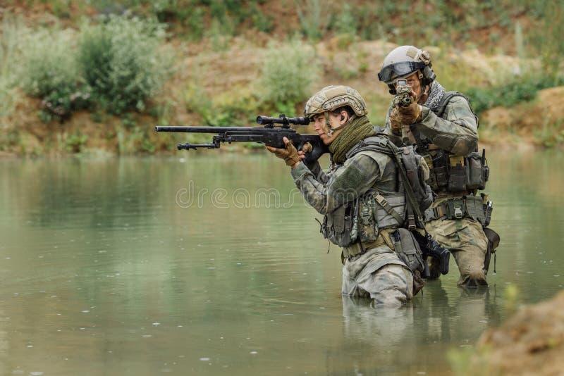 Militair team die de rivier kruisen onder brand stock foto