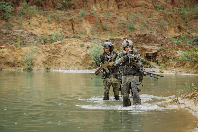 Militair team die de rivier kruisen onder brand royalty-vrije stock afbeelding