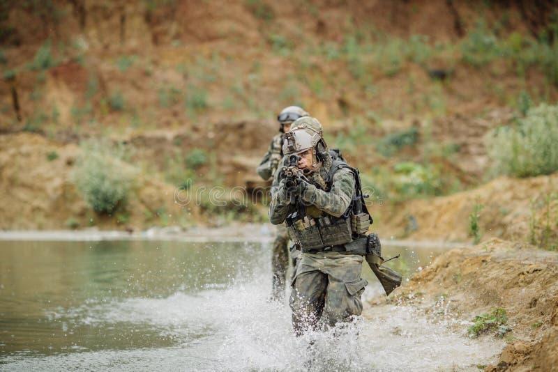 Militair team die de rivier kruisen onder brand stock fotografie
