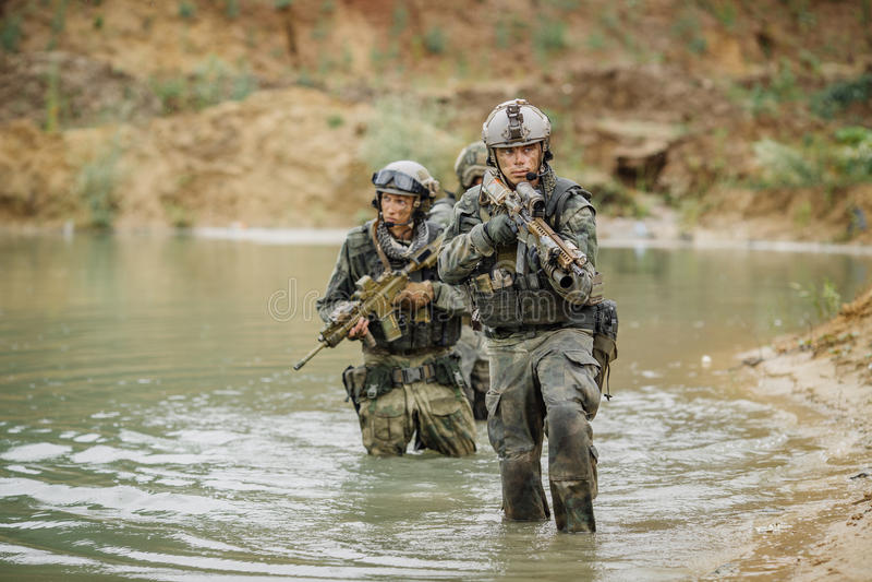 Militair team die de rivier kruisen onder brand royalty-vrije stock fotografie
