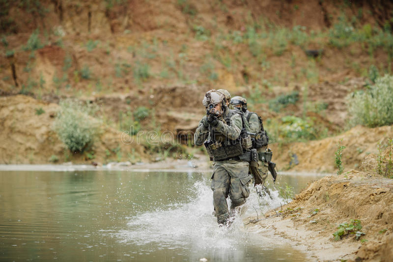 Militair team die de rivier kruisen onder brand stock afbeeldingen