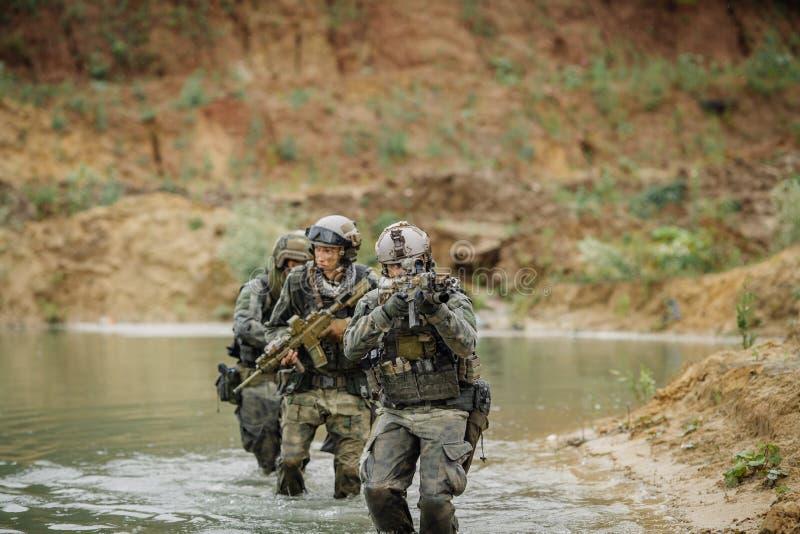 Militair team die de rivier kruisen onder brand royalty-vrije stock afbeeldingen
