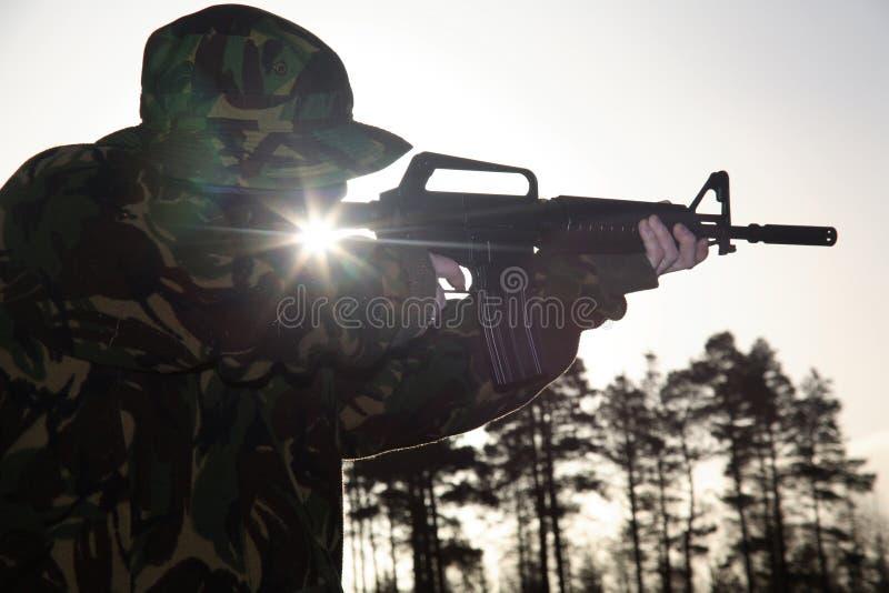 Militair, zijn Geweer en Zon stock afbeeldingen