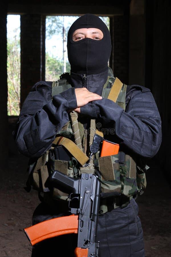 Militair in zwart masker dat kanon ak-47 houdt royalty-vrije stock afbeelding