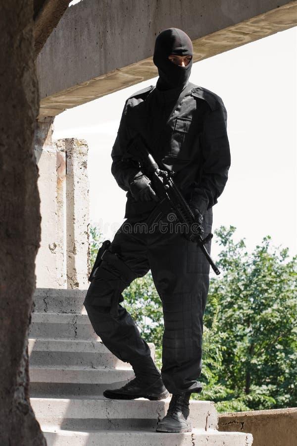 Militair in zwarte eenvormig met geweer stock foto's