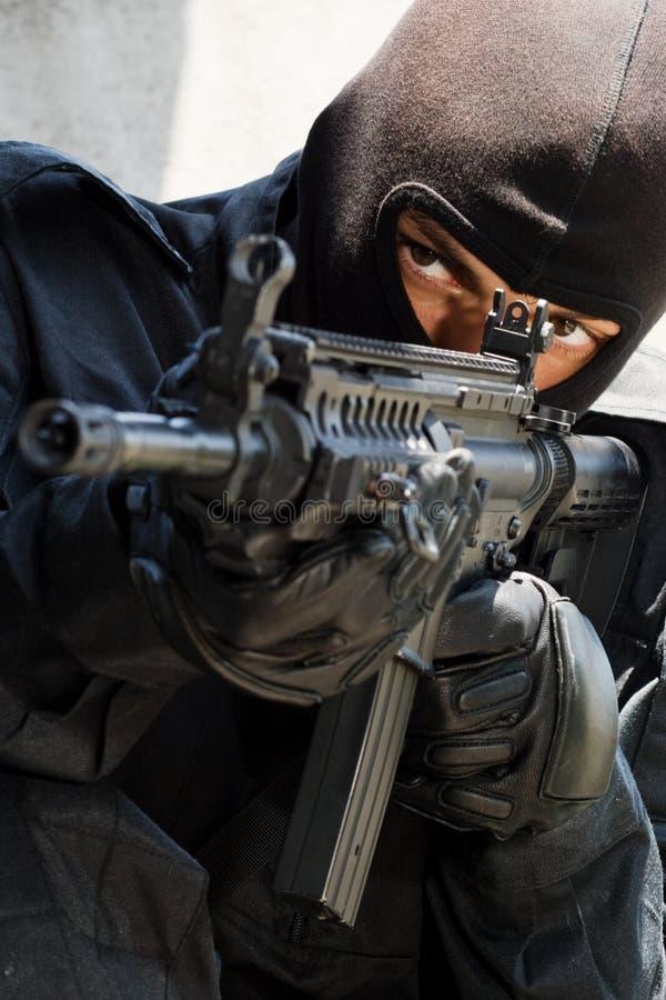 Militair in zwarte eenvormig met geweer royalty-vrije stock fotografie