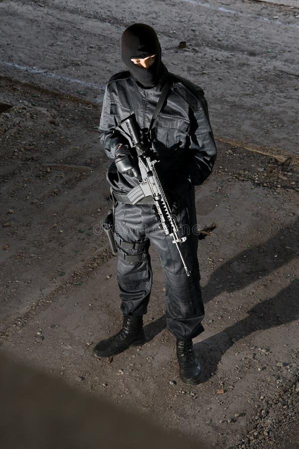Militair in zwarte eenvormig met geweer m-4 royalty-vrije stock afbeeldingen