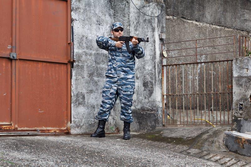 Militaire caucasien dans l'esprit protecteur de porte de fer de combat en zone urbaine images libres de droits