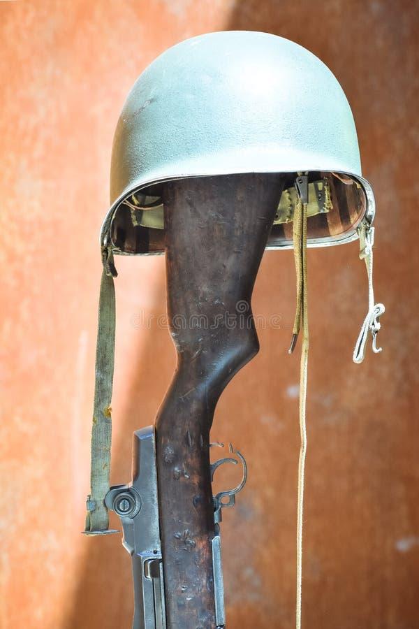 Militaire die helm op een vuurwapen wordt gesteund Concept onbekende militair stock fotografie