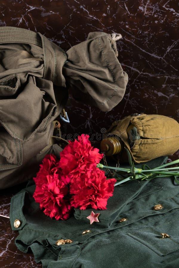 Militaire eenvormig, de fles, de zak en de rode bloemen ligt op de achtergrond van een bruine marmeren plak stock fotografie