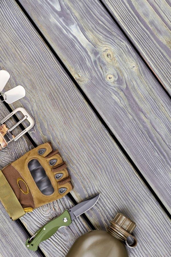 Militaire handschoen, mes en fles op hout royalty-vrije stock foto's